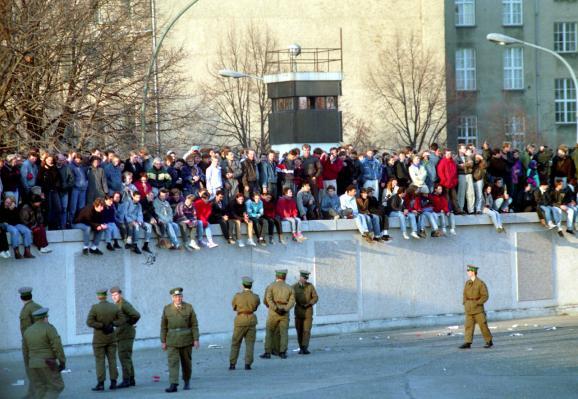Une foule se dresse sur le mur de Berlin tandis que des soldats les surveillent d\'en bas, le 10 novembre 1989.