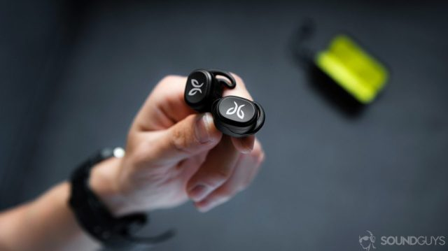 An image of the Jaybird Vista earbuds being held in a hand with the open charging case in the background.