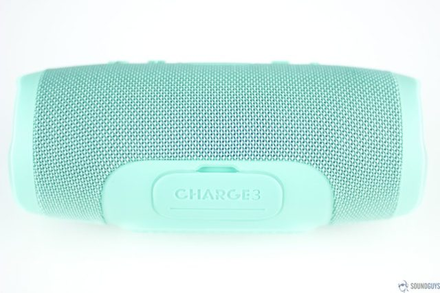 Pictured is the teal JBL Charge 3 Bluetooth speaker on its side showing the flap protecting the ports.