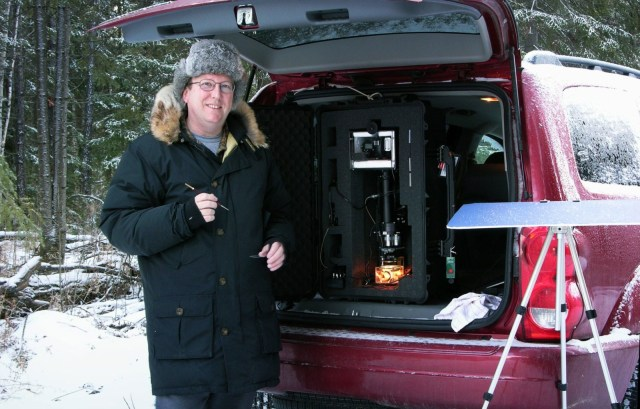 a man next to a device in the back of his truck