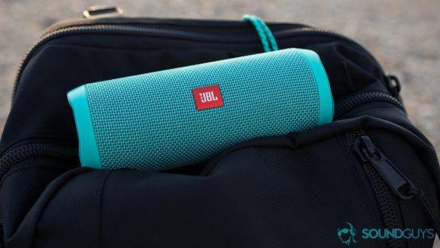 A picture of the JBL Flip 4 waterproof speakers in aqua blue on top of a black backpack.