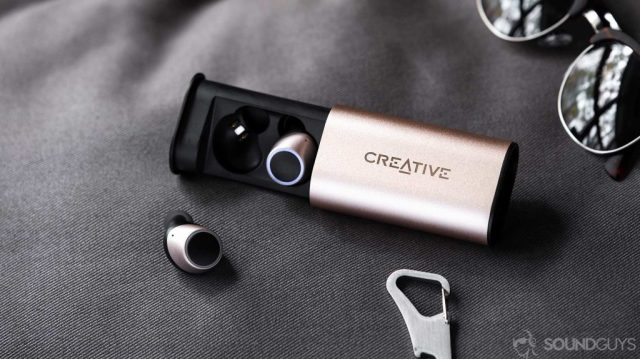 An image of the Creative Outlier Air earbuds, one in the case and one out, with sunglasses in the back right corner.