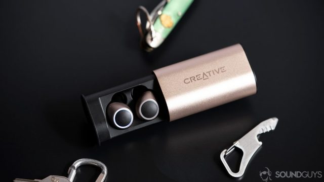 An image of the Creative Outlier Air earbuds in the case surrounded by an army knife, bottle opener, and carabiner on a black surface.