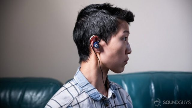 A photo of the Massdrop x Empire Ears Zeus earbuds being worn by a woman looking to the right of the frame.