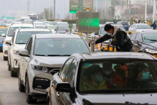 Un contrôle de température des passagers, à un péage de la ville de Wuhan, en Chine, le 23 janvier.