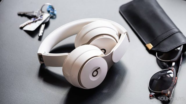 A photo of the Beats Solo Pro on-ear noise cancelling headphones folded inward on a black surface and surrounded by sunglasses and keys.