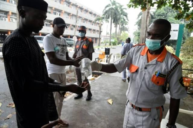 Des agents de sécurité désinfectent des visiteurs à l'hôpital de Lagos, le 28 février 2020 ( AFP / PIUS UTOMI EKPEI )