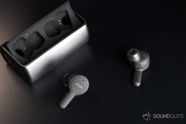 Angled downward image of the A picture of the RHA TrueConnect open charging case with the earbuds facing the lens in different directions; the closer 'bud shows the RHA logo.
