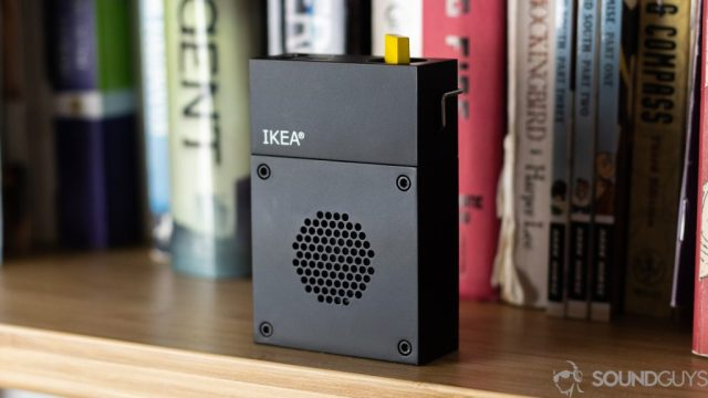 Pictured is the Frekvens Portable speaker on a shelf in front of books.