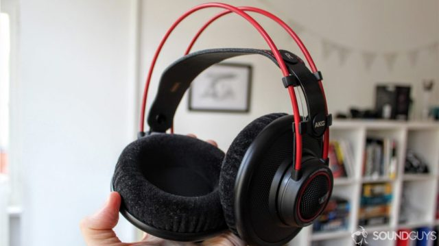 Man holding AKG K7XX's in hand with velour earpads and red frame in focus.