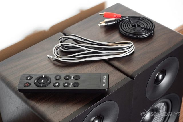 Fluance Ai40 review: The remote, adapter wire, and RCA cable all shown on top of the speaker units.