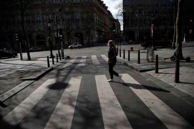 Une femme portant un maque près des Champs-Elysées, le 15 mars à Paris.