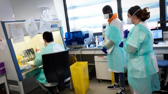 Du personnel médical testeun échantilon prélevé chez un patient potentiellement atteint de Covid-19, le 26 février 2020 dans un laboratoire de l\'IHU de Marseille.