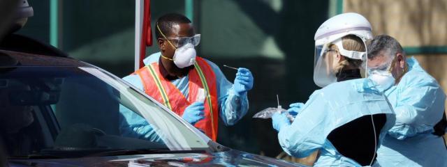 """Des personnels soignants procèdent à un dépistage du coronavirus à un \""""drive\"""" à Denver, dans le Colorado (Etats-Unis), le 11 mars 2020."""