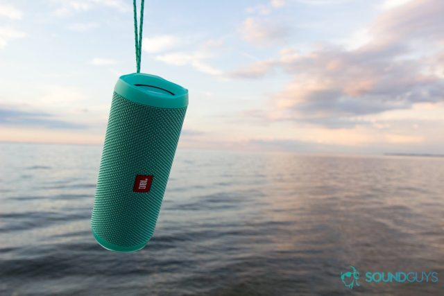 The teal JBL Flip 4 being held up by its string over the water.