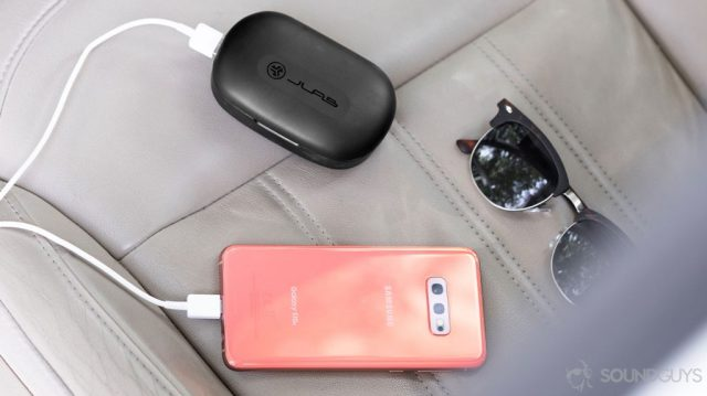 The JLab JBuds Epic Air charging case charging a Samsung Galaxy S10e in Flamingo Pink. A pair of sunglasses are next to the items on a leather car seat.