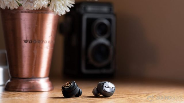 A photo of the Sol Republic Amps Air Plus true wireless noise cancelling earbud compared to the JLab JBuds Air Icon.