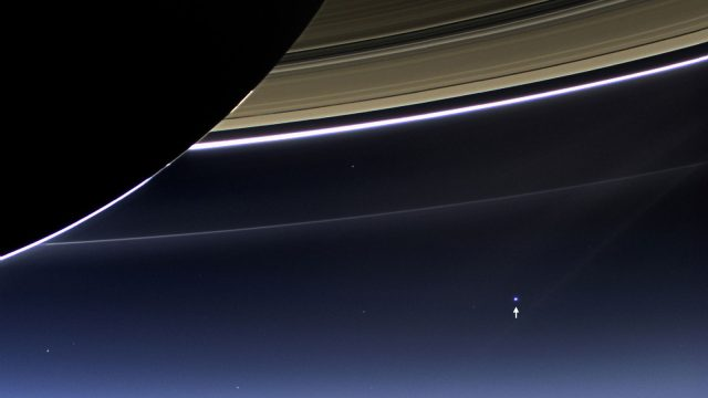 saturn's rings backlit by sun with tiny Earth
