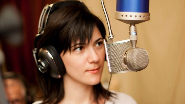 A woman using the Blue Bottle tube microphone in a studio - microphone types explained.