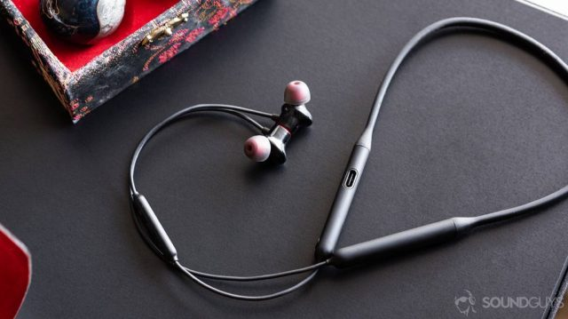 Conference calls - OnePlus Bullets Wireless 2: Full image of the earbuds and neckband with the cable curling up and around on a black table.