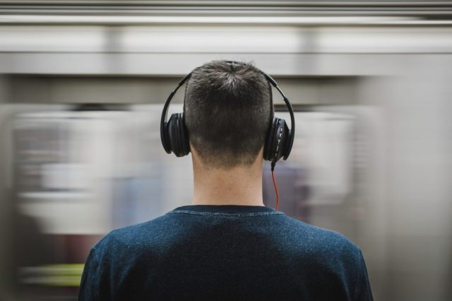 """A photo of a young man wearing headphones in front of a moving train, for the article """"best headphones for kids."""""""