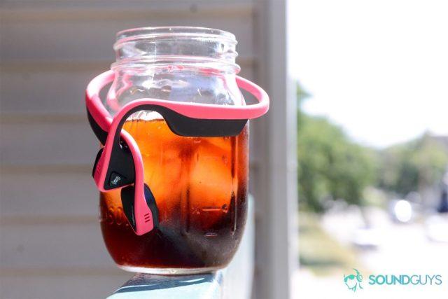Bone conduction headphones: Aftershokz Trekz Titanium wrapped around a cold brew coffee in mason jar.