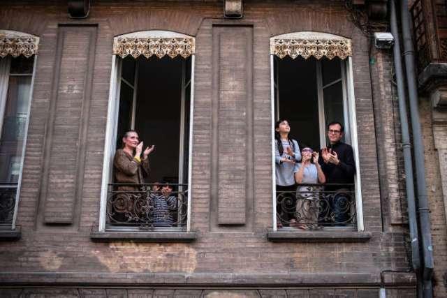 Mardi 14 avril, Toulouse, 20 heures, des familles de la Rue Raymond IV applaudissent à la fenêtre pour rendre hommage aux personnels hospitaliers.