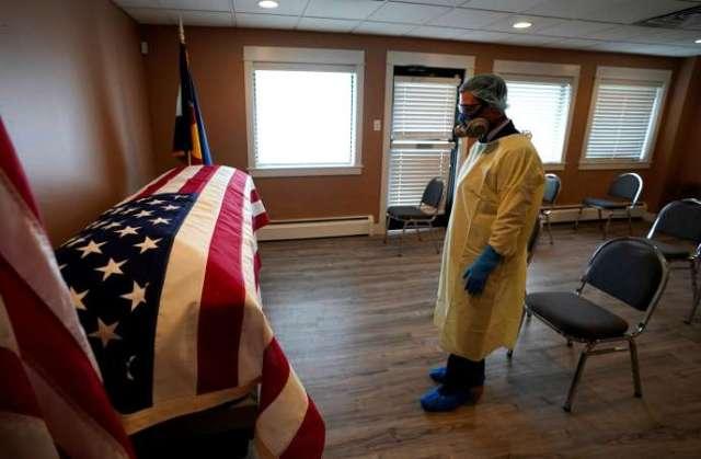Le directeur des pompes funèbres pour les vétérans devant le cercueil de George Trefren, 90 ans, un vétéran de la guerre de Corée, décédé des suites du Covid-19, le 23 avril à Denver dans le Colorado.