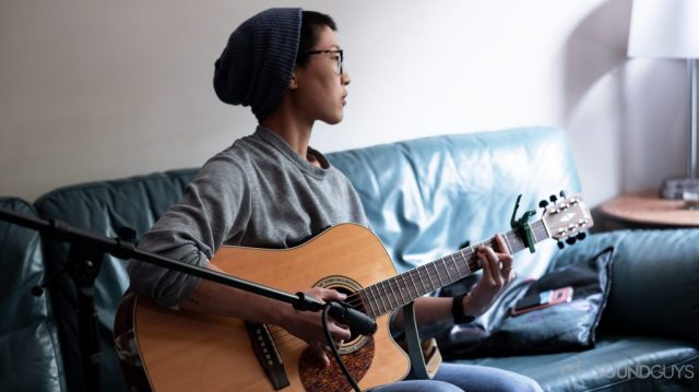 A picture of woman playing guitar and recording it with the Shure SM57 XLR mic, which is often compared to the Shure SM58.