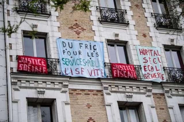 Une banderole portant l'inscription «De l'argent pour les services publics»affichée sur un balcon, le jour de la Fête des travailleurs, le 1er mai 2020, à Paris.