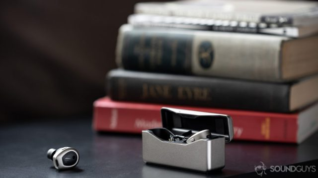A picture of the Edifier TWS NB true wireless noise cancelling earbuds, one in the open case and one outside of it, in front of a stack of books.
