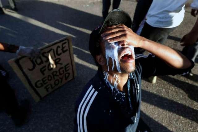 Un manifestant apaise les brûlures des gazs lacrymogènes avec du lait, le 29 mai dans les rues de Minneapolis, quatre jours après la mort de George Floyd.
