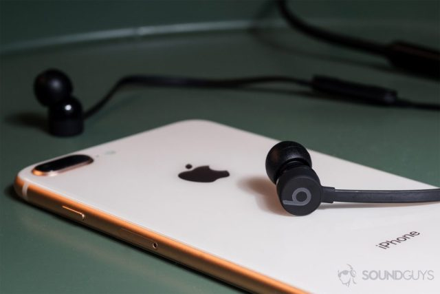 BeatsX review: The BeatsX on an iPhone 8 Plus in rose gold both resting on a green end table.