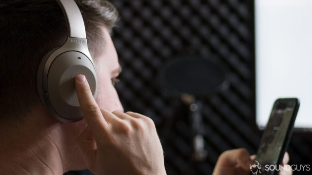 A photo of the active noise canceling Sony WH-1000X M2 wireless Bluetooth headphones being used to activate the Google Assistant on a Google Pixel XL.