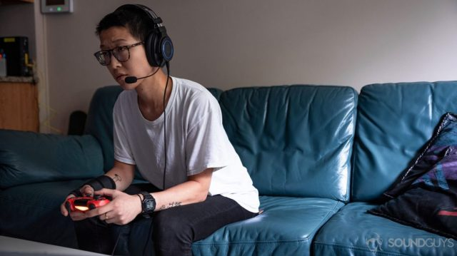 A woman playing on a PlayStation 4 with the Audio-Technica ATH-G1 headset plugged directly into the controller.