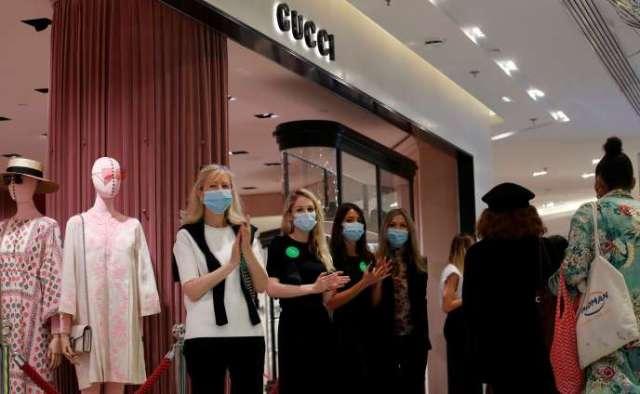 Les employées d'un magasin de vêtements accueillent leurs clients le jour de l'ouverture des soldes, au Printemps à Paris, le 15 juillet.