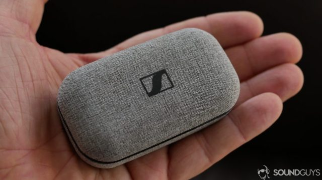 A photo of the Sennheiser Momentm True Wireless in the battery case, resting on a hand.