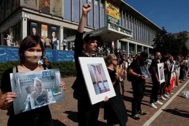 Des manifestants brandissent des photos de compatriotes blessés lors des rassemblements contre le président biélorusse, Alexandre Loukachenko, le 15 août à Minsk.