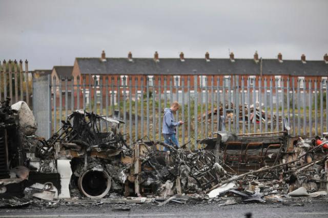 Un passant devant l'autobus qui a été détourné et incendié sur Shankill Road, à Belfast, le 7 avril 2021.