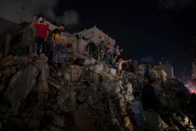 Des Palestiniens se tiennent sur les décombres alors que le cessez-le-feu vient d'être déclaré entre Israël et le Hamas, à Gaza, le 21 mai 2021.