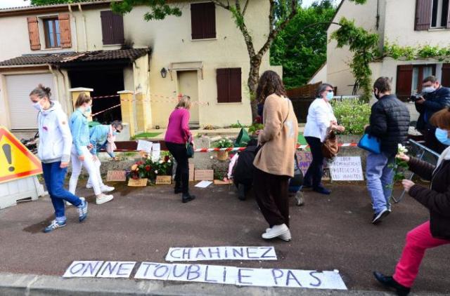 Des gens déposent des fleurs devant la maison de Chahinez Boutaa, brûlée vive par son mari, à Mérignac (Gironde), le 5 mai.