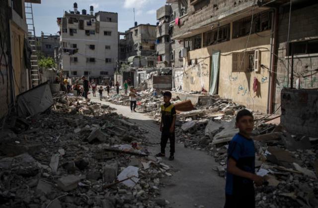 De jeunes Palestiniens au milieu des décombres causés par une frappe aérienne israélienne, à Gaza, le 17 mai 2021.