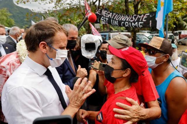 Le président Emmanuel Macron discute avec une victime d'un essai nucléaire qui participe à une manifestation, à son arrivée sur l'île de Moorea, le 27 juillet 2021.