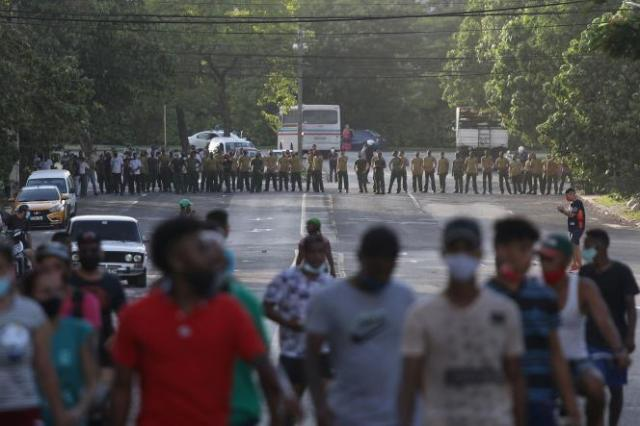 Des manifestants s'éloignent des soldats de l'armée qui bloquent une route, lors d'une manifestation, dans le contexte de l'épidémie de coronavirus, à La Havane, le 11 juillet 2021.