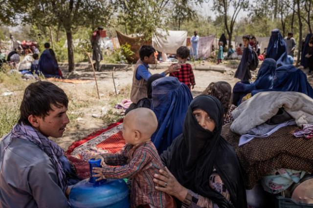 Jamshid Alizada (à gauche), avec des membres de sa famille dans un camp de fortune abritant des réfugiés à Sarai Shamali, à Kaboul, en Afghanistan, le 10 août 2021.
