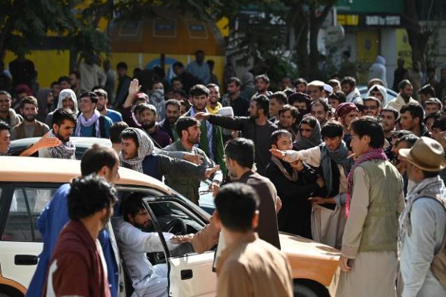 Des Afghans rassemblés devant un bâtiment bancaire fermé, à Kaboul, le 28 août 2021.