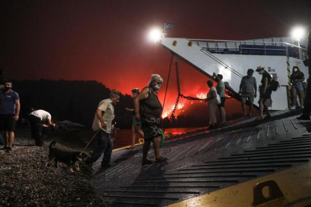 Des habitants évacués à bord d'un ferry alors que le feu s'approche du village de Limni, en Grèce, le 6août2021.