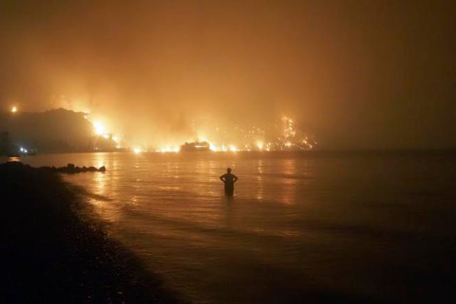 Un homme regarde les flammes gagner la plage de Kochyli, près du village de Limni, sur l'île d'Eubée, le 6août2021.