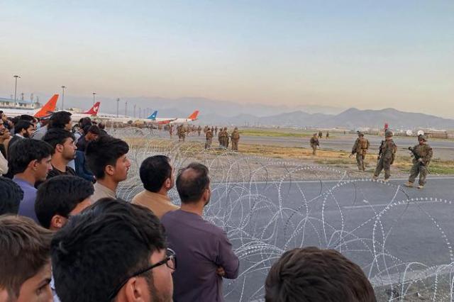 Des Afghans font face aux soldats américains à l'aéroport de Kaboul, le 16août 2021.