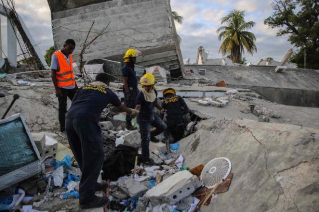 Des pompiers haïtiens fouillent les décombres d'un immeuble effondré aux Cayes, dimanche 15 août.